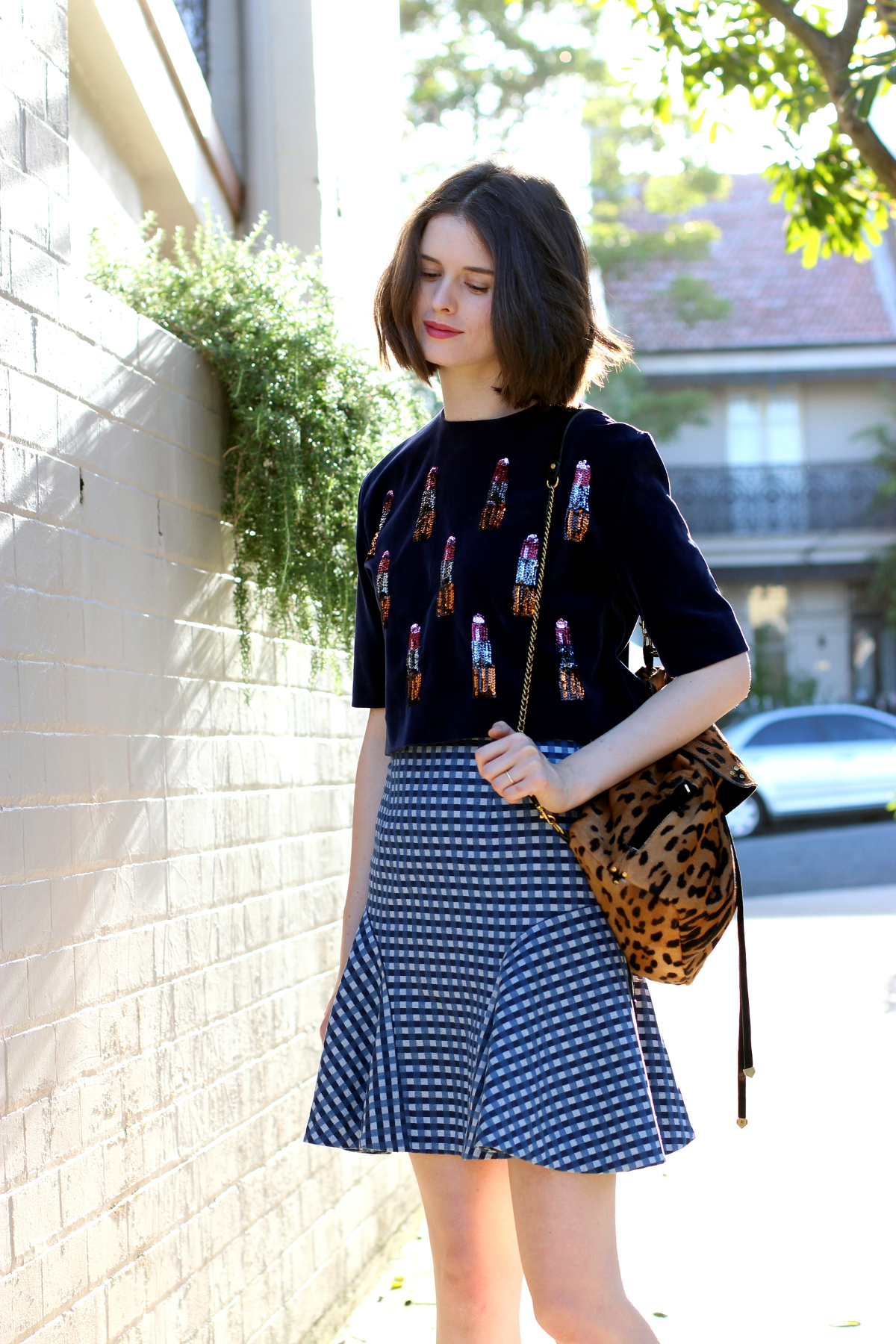 BYCHILL SYDNEY STREET STYLE Chloe Hill Wearing House of Holland navy velvett op with sequin lipstick detail, Bianca Spender blue gingham check skirt and Jerome Dreyfuss leopard print ponyhair backpack